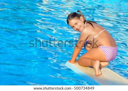 Real toddler girl at swimming pool, summer vacation concept