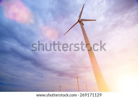 Real wind turbine against sunlight - stock photo