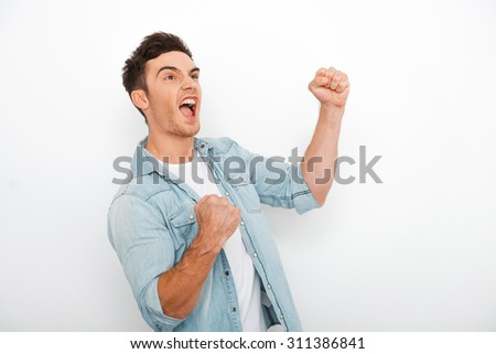 Real winner. Excited young man keeping arms raise and expressing positivity while standing against white background - stock photo