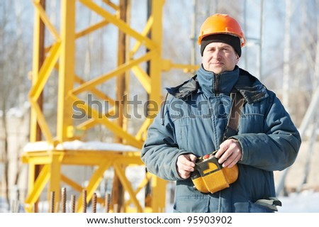 Real worker builder operator with tower crane remote control equipment at construction area site - stock photo