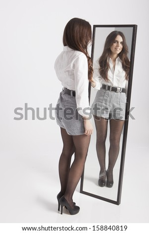 real young woman looking in a mirror - stock photo