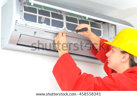 Real young woman worker adjusting air conditioner system