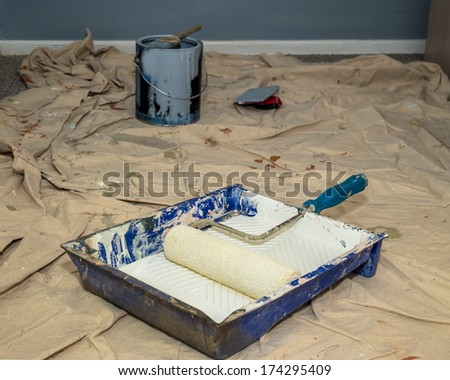 Realistic image of paint pan and roller on drop cloth during interior painting project - stock photo