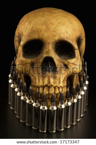 realistic-looking model of human skull dramatically lit and surrounded by rifle cartridges. - stock photo