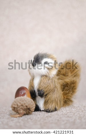 Realistic Miniature Squirrel, Animal Replica Prop Fur Toy, for Decoration, Selective Focus, isolated on soft brown background (copy space, empty space for text on top) - stock photo