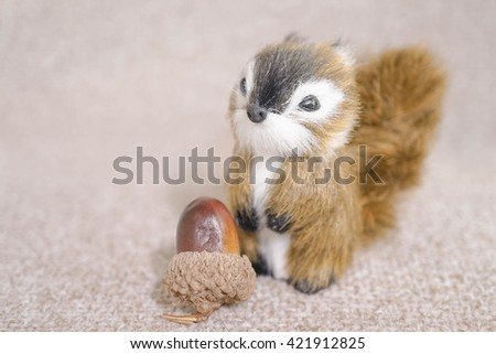 Realistic Miniature Squirrel, Animal Replica Prop Fur Toy, for Decoration, Selective Focus, isolated on soft brown background (copy space, empty space for text on the left)  - stock photo