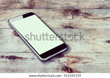 Realistic mobile phone iphon style mockup with blank screen on wooden background. Highly detailed illustration. - stock photo