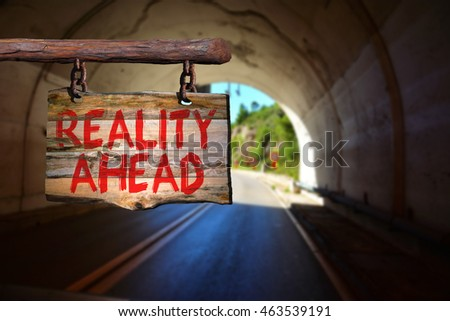 Reality ahead motivational phrase sign on old wood with blurred background