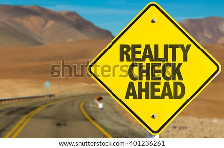 Reality Check Ahead sign on desert road - stock photo