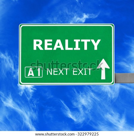 REALITY road sign against clear blue sky - stock photo