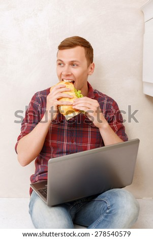 Really tasty. Young man looking aside eating big sandwich and holding notebook.