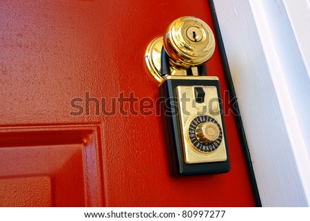 Realtor combination lock box safety key holder on doorknob of a house for sale entrance door for a real estate resale transaction - stock photo