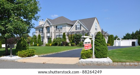 Realtor For Sale Sign on front yard of beautiful landscaped large brick suburban home on sunny clear blue sky day - stock photo