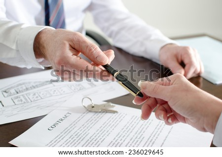 Realtor giving a pen to sign a contract - stock photo