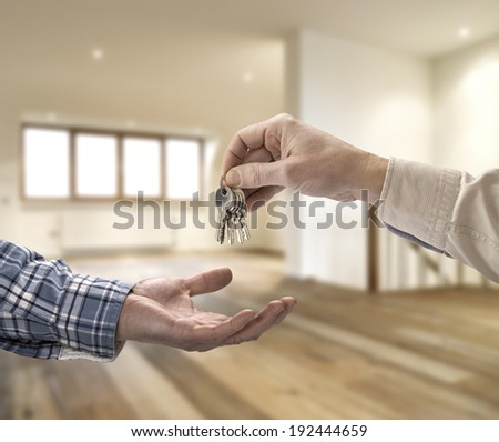 Realtor giving house key to buyer in empty room - stock photo