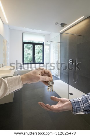 Realtor giving house key to buyer in Luxury Bathroom Estate Home - stock photo