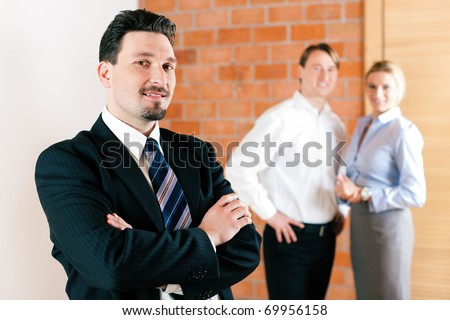 Realtor in an empty apartment with some clients looking for real estate - stock photo
