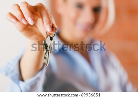 Realtor is giving the keys to an apartment to some clients � focus on the keys - stock photo