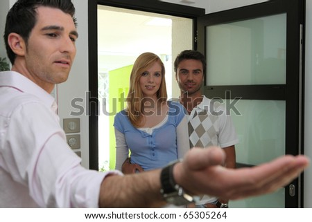 Realtor making a visit of a house to a couple - stock photo