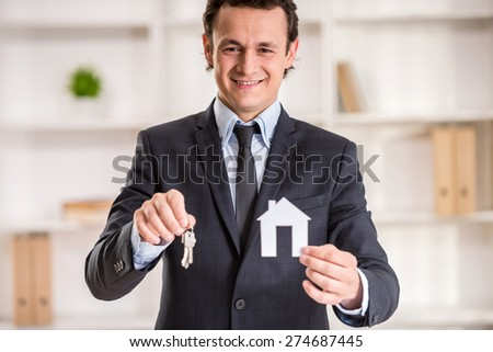 Realtor man is showing a model of home and keys. - stock photo