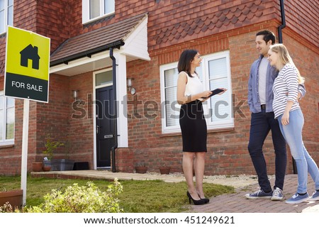 Realtor Outside House For Sale With Young Couple - stock photo
