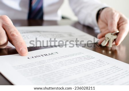 Realtor showing a contract with his finger - stock photo