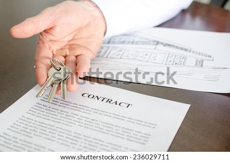 Realtor showing house keys over a contract - stock photo