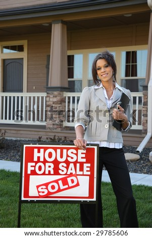 Realtor standing in front of home with SOLD sign