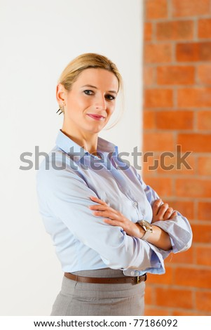Realtor standing with folded arms in an empty apartment - stock photo