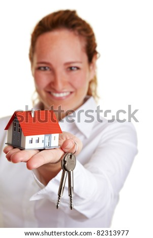 Realtor woman offering house keys and small house - stock photo