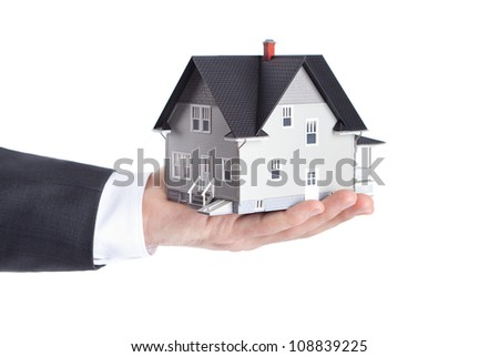Realty concept - hand holding house architectural model, isolated - stock photo