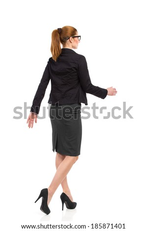 Rear angle view of walking businesswoman in black suit, skirt and high heels. Full length studio shot isolated on white. - stock photo