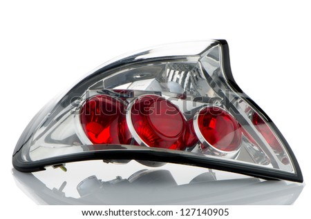 Rear automobile lamp detail on white reflective background. - stock photo