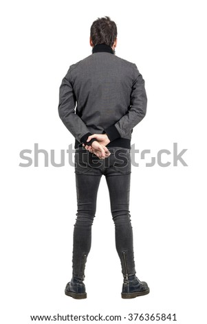 Rear back view of man in tight jeans and gray jacket looking away. Full body length portrait isolated over white studio background.