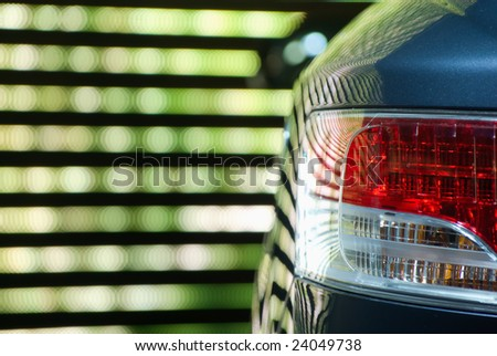 Rear Car Light against a neon multicolored backgroung - stock photo