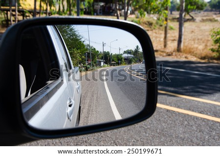 rear car mirror and rural road view - stock photo