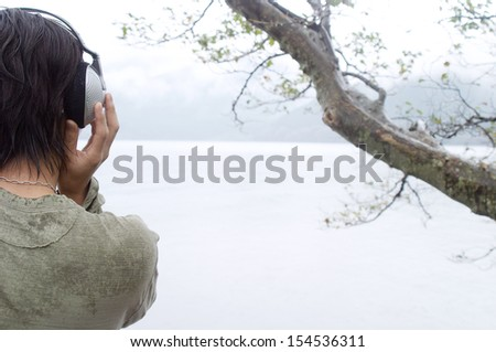 Rear close up view of a young japanese man contemplating a lake and mountains landscape and listening to music using his headphones during a rainy autumn day, outdoors. - stock photo