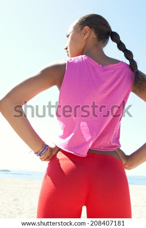 Rear colorful portrait of attractive healthy black young woman standing on a white sand beach relaxing on vacation during a sunny day contemplating the sea while doing sport. Recreational lifestyle. - stock photo