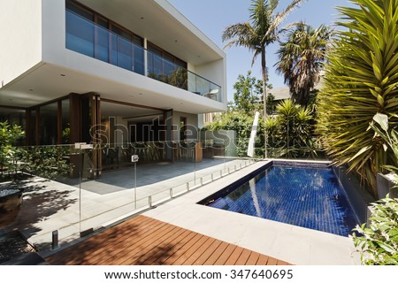 Rear garden of a contemporary Australian home with tiled swimming pool - stock photo