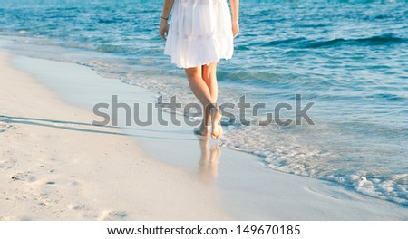 Rear lower body section of a young woman walking along a white sand beach shore at sunset, taking steps and relaxing with an intense blue sea during a summer vacation. - stock photo