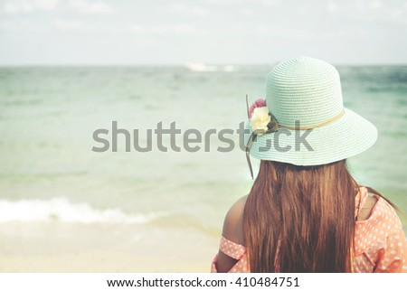 Rear of happy young woman wear straw hat - stand on the beach in summer. Vintage color tone - stock photo