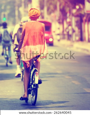 Rear of the women tourists by riding bicycle in the city. vintage tone Blurred effect - stock photo