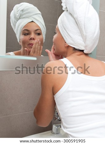 Rear portrait and face reflection of a beautiful young woman applying nourishing cream on her face, looking at herself in a bathroom mirror, with towel wrapping her hair, home interior. Skin care. - stock photo