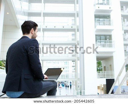 Rear portrait of a young businessman sitting indoors with laptop - stock photo