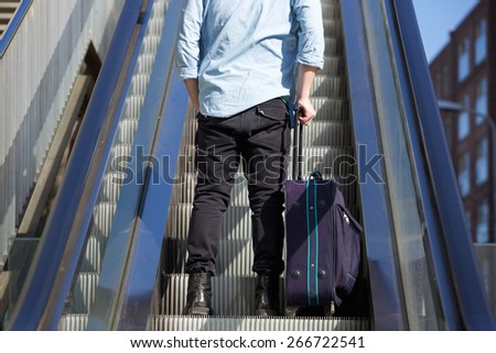 Rear portrait of a young man standing on escalator with bag - stock photo