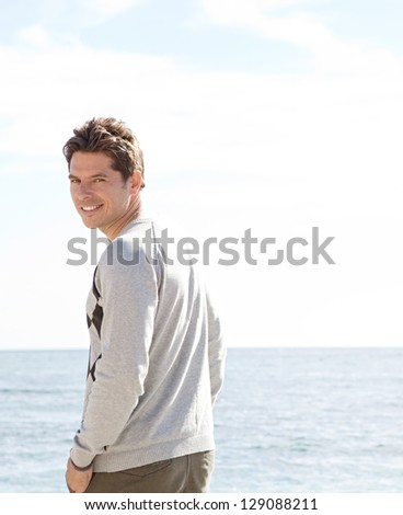 Rear portrait view of an attractive smart man standing by the sea, turning to smile at the camera against a blue sky. - stock photo