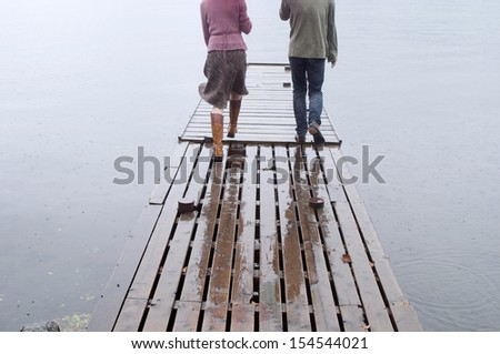 Rear romantic view of a young couple walking together on a wooden pier on a lake during a rainy autumn day outdoors with water drops falling. - stock photo