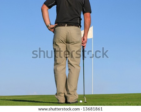 Rear shot of a golfer reading the green prior to putting. - stock photo