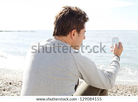 "Rear side close up view of a smart man sitting on a pebble beach on a sunny winter day, taking a photograph of the sea with his ""smart phone"". - stock photo"