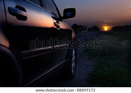 Rear-side view of a luxury car on sunset - stock photo